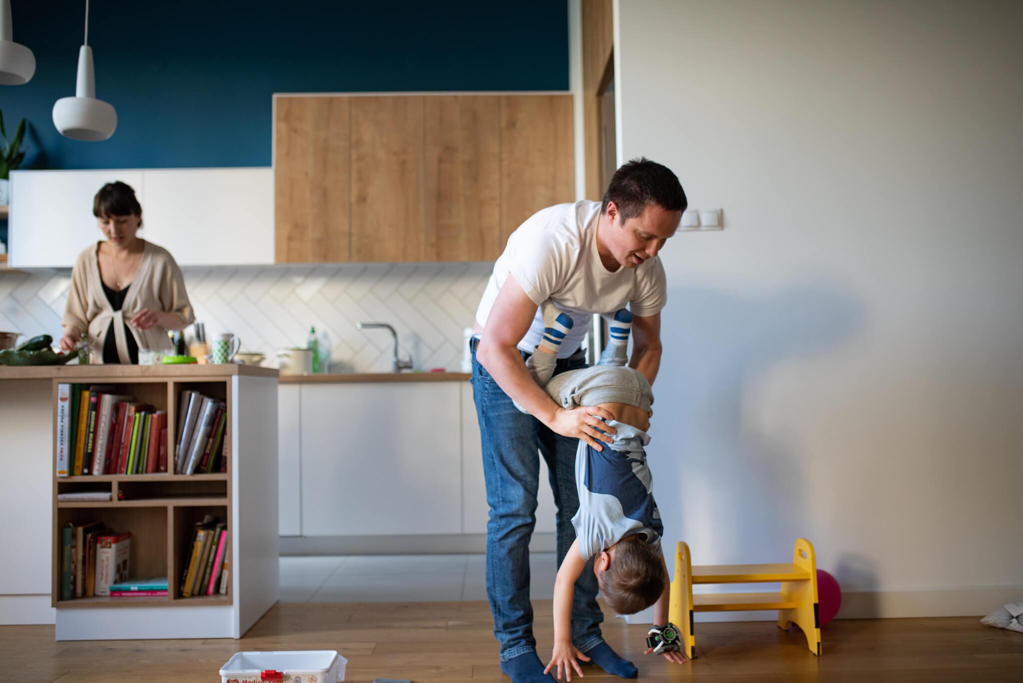 tata-robiący-fikołka-dziecku-w-kuchni