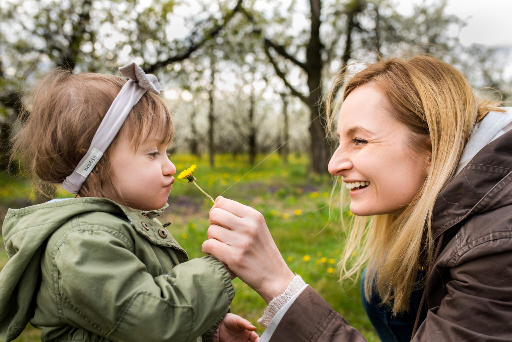 uśmiechnięta mama dająca do powąchania kwiatek córce podczas sesji rodzinnej w sadzie