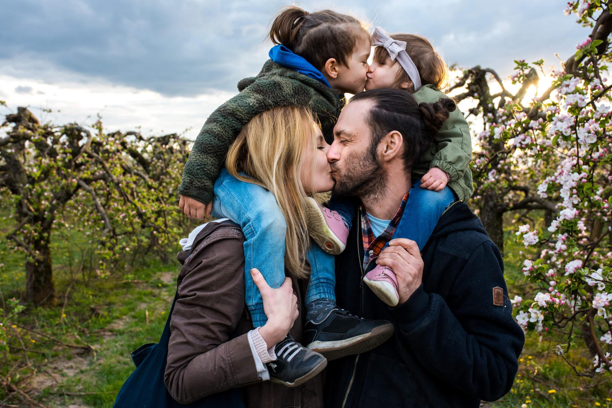 rodzice trzymający na barana swoje dzieci podczas sesji rodzinnej w sadzie