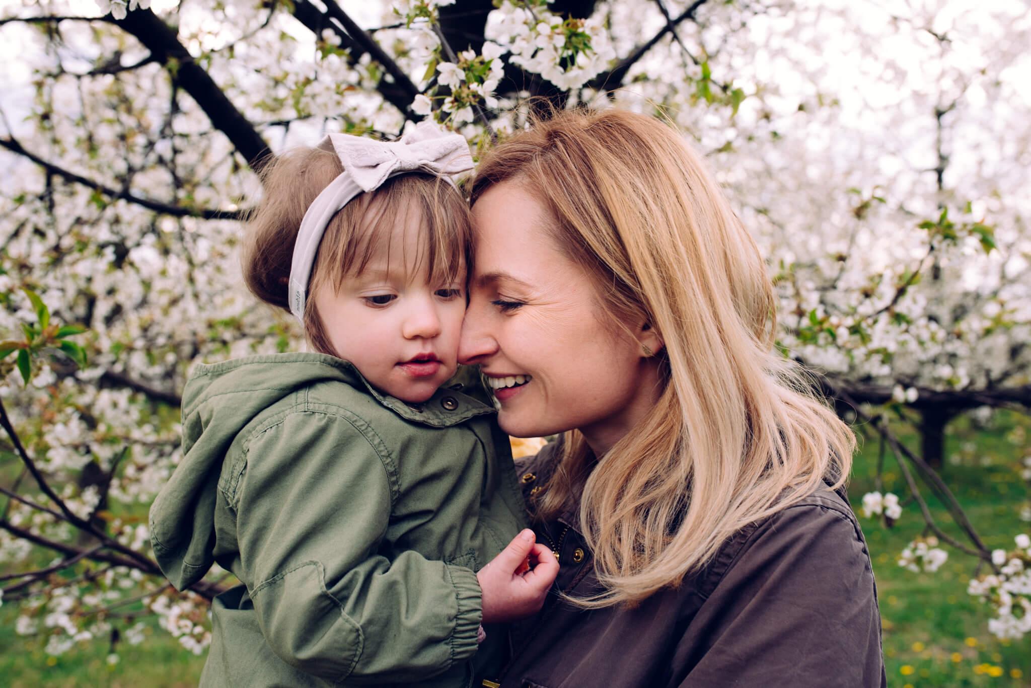 mama przytulająca córkę w sadzie podczas sesji rodzinnej