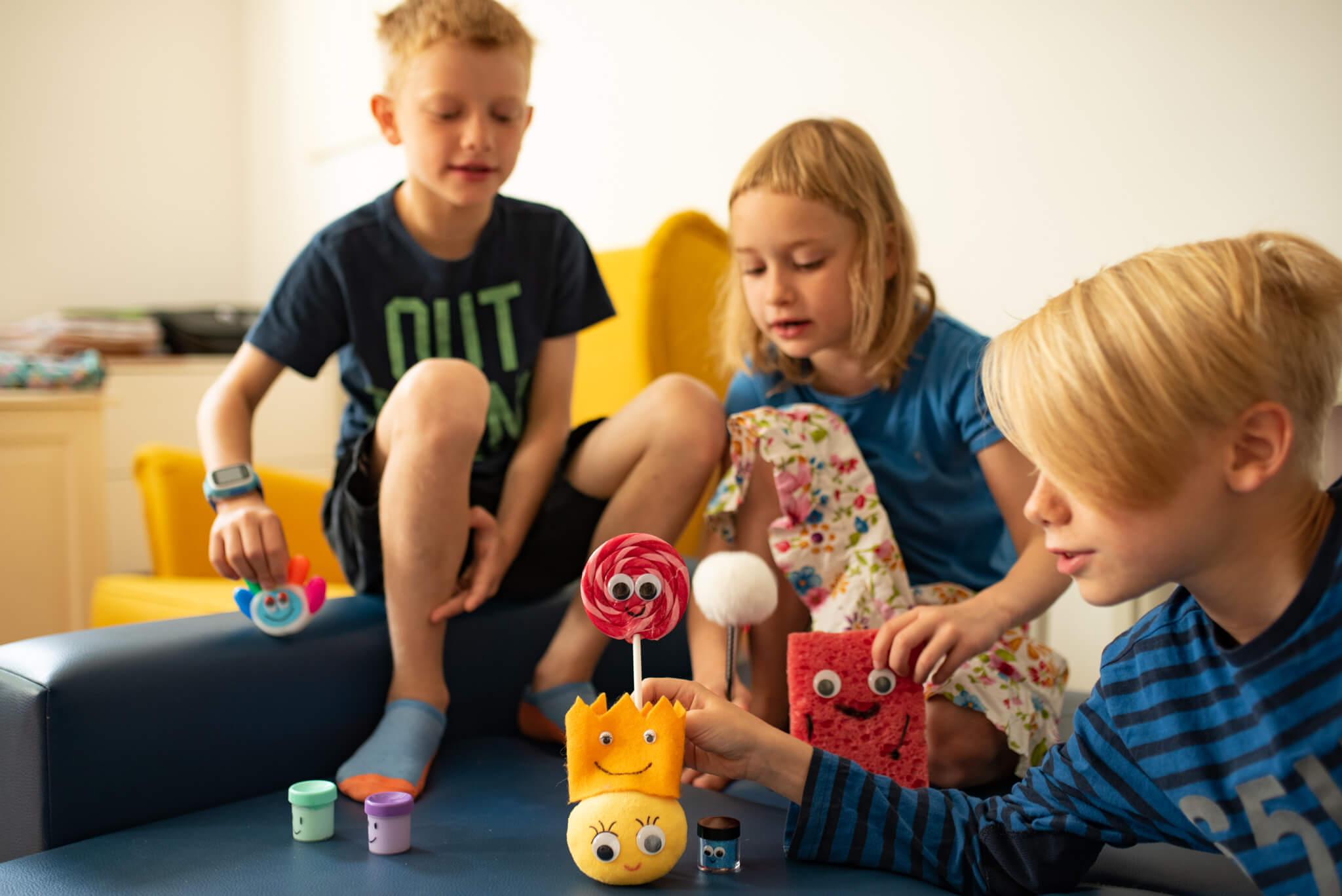 trójka dzieci bawiąca się z przedmiotami na których przylepione są oczy