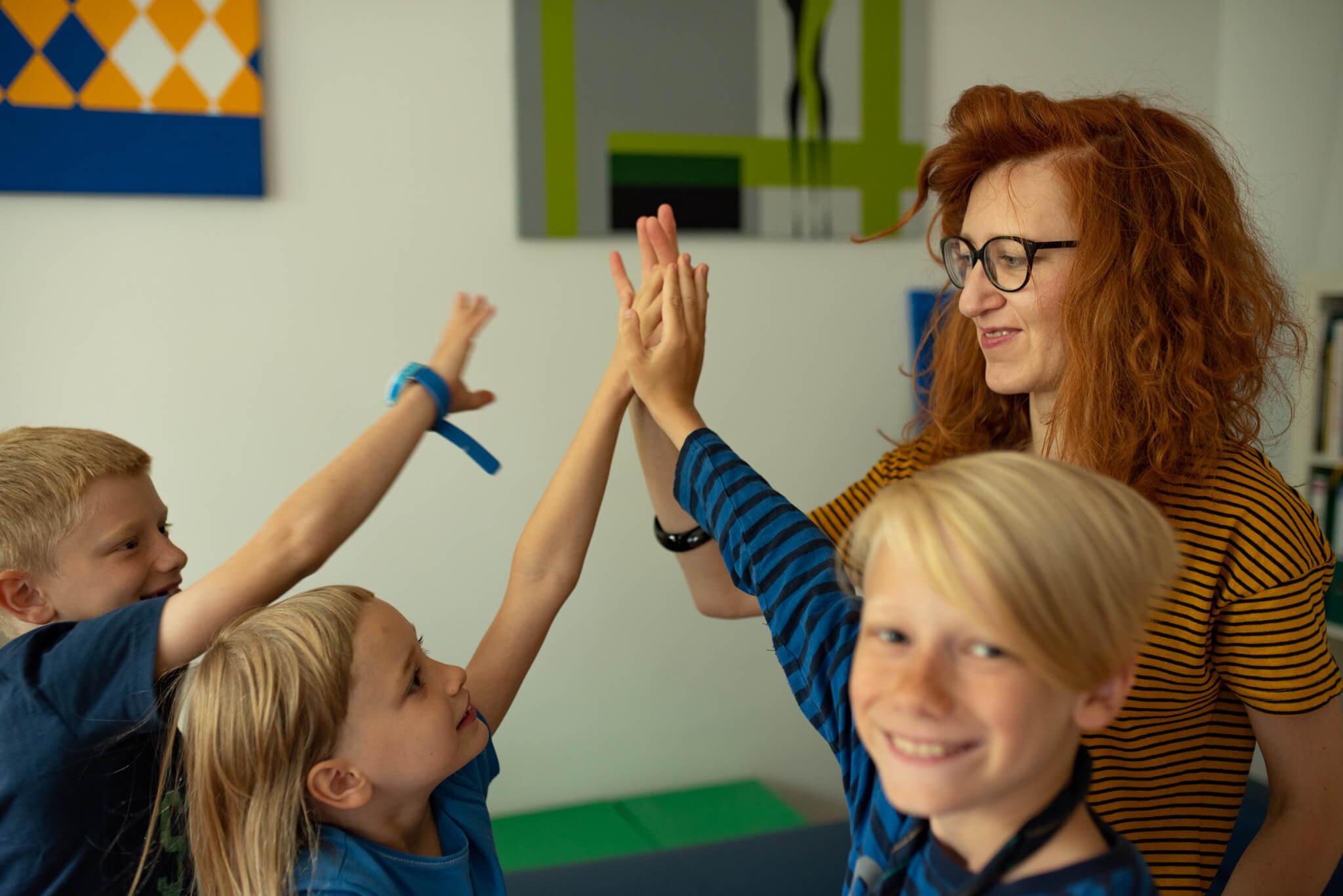 kobieta przybijająca piątkę z trójką rodzeństwa podczas lekcji języka angielskiego