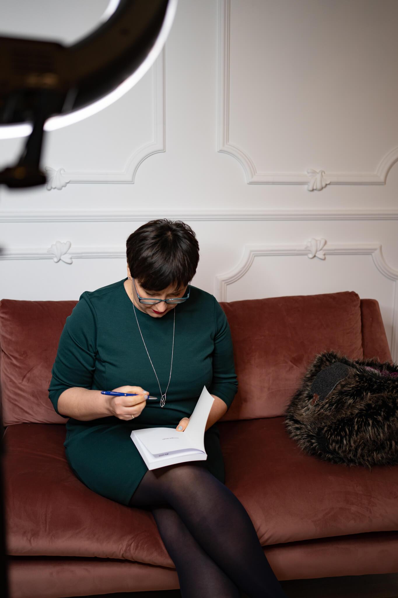 kobieta siedząca na kanapie w studio podpisująca swoją książkę