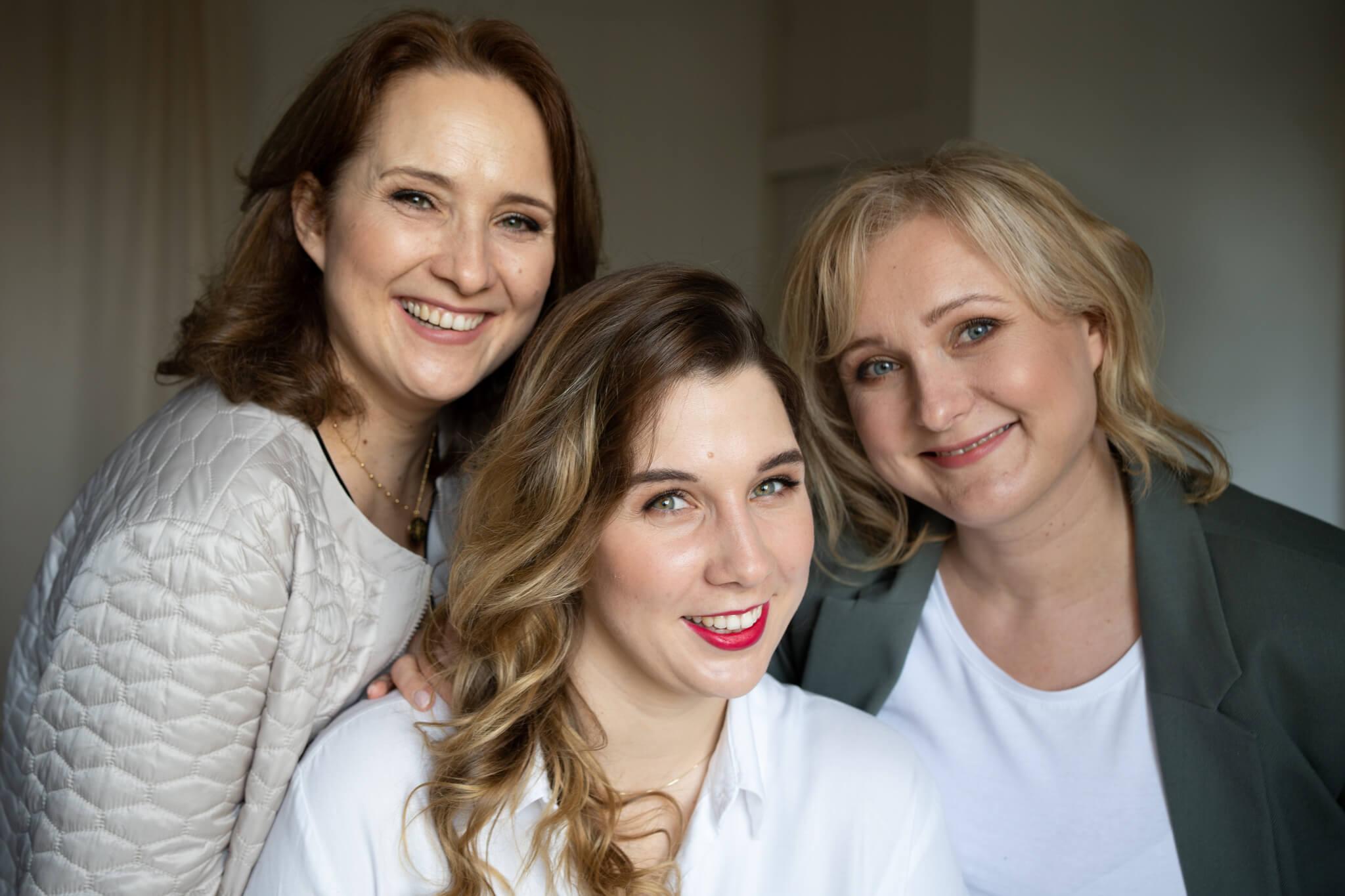 trzy kobiety uśmiechają się w stronę obiektywu