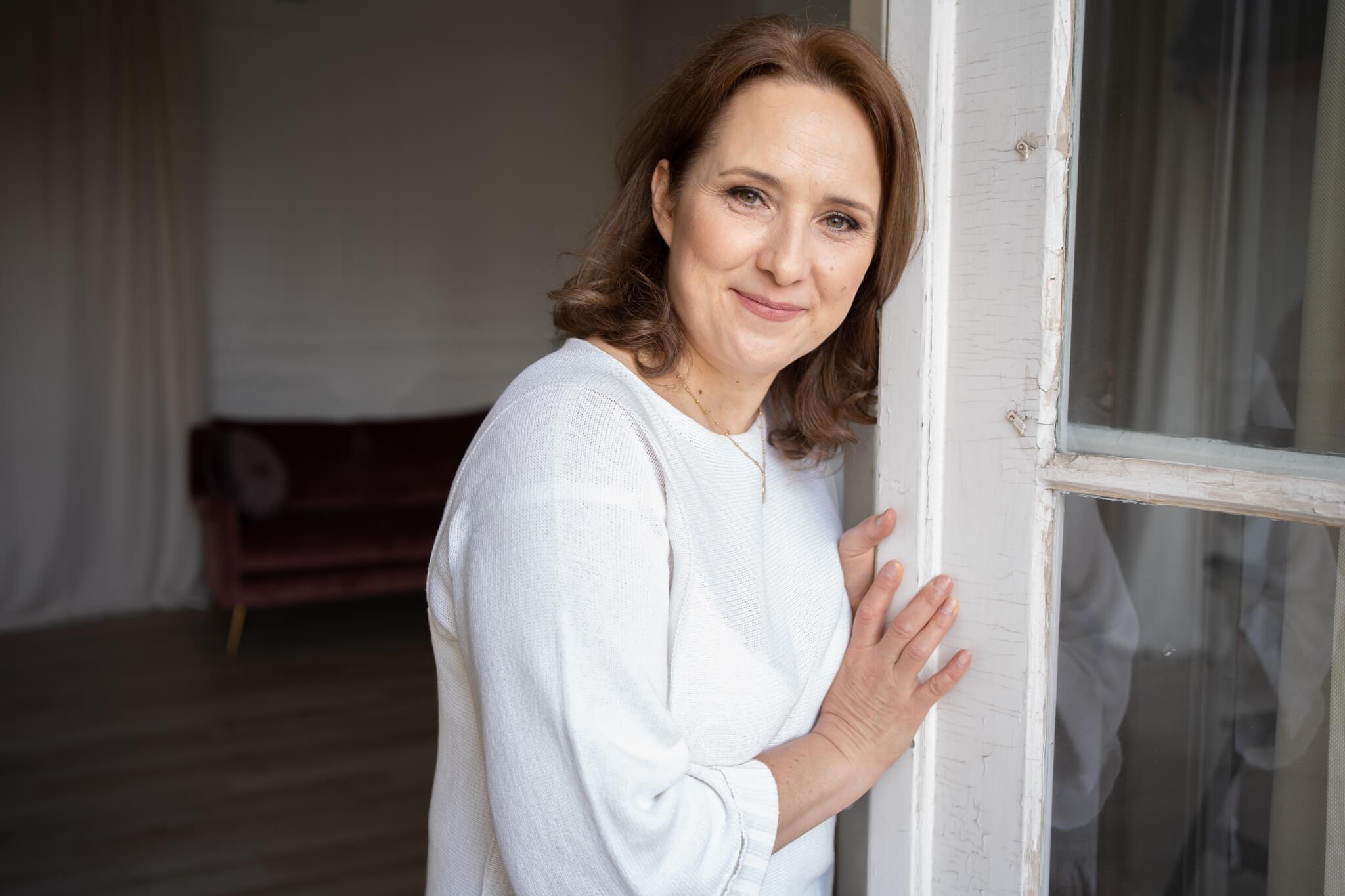 kobieta opierająca się o uchylone drzwi z tarasy w studio