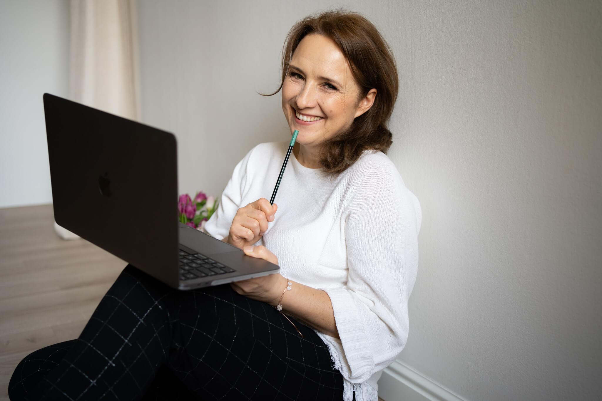 kobieta z laptopem opierająca się o ścianę w studiu