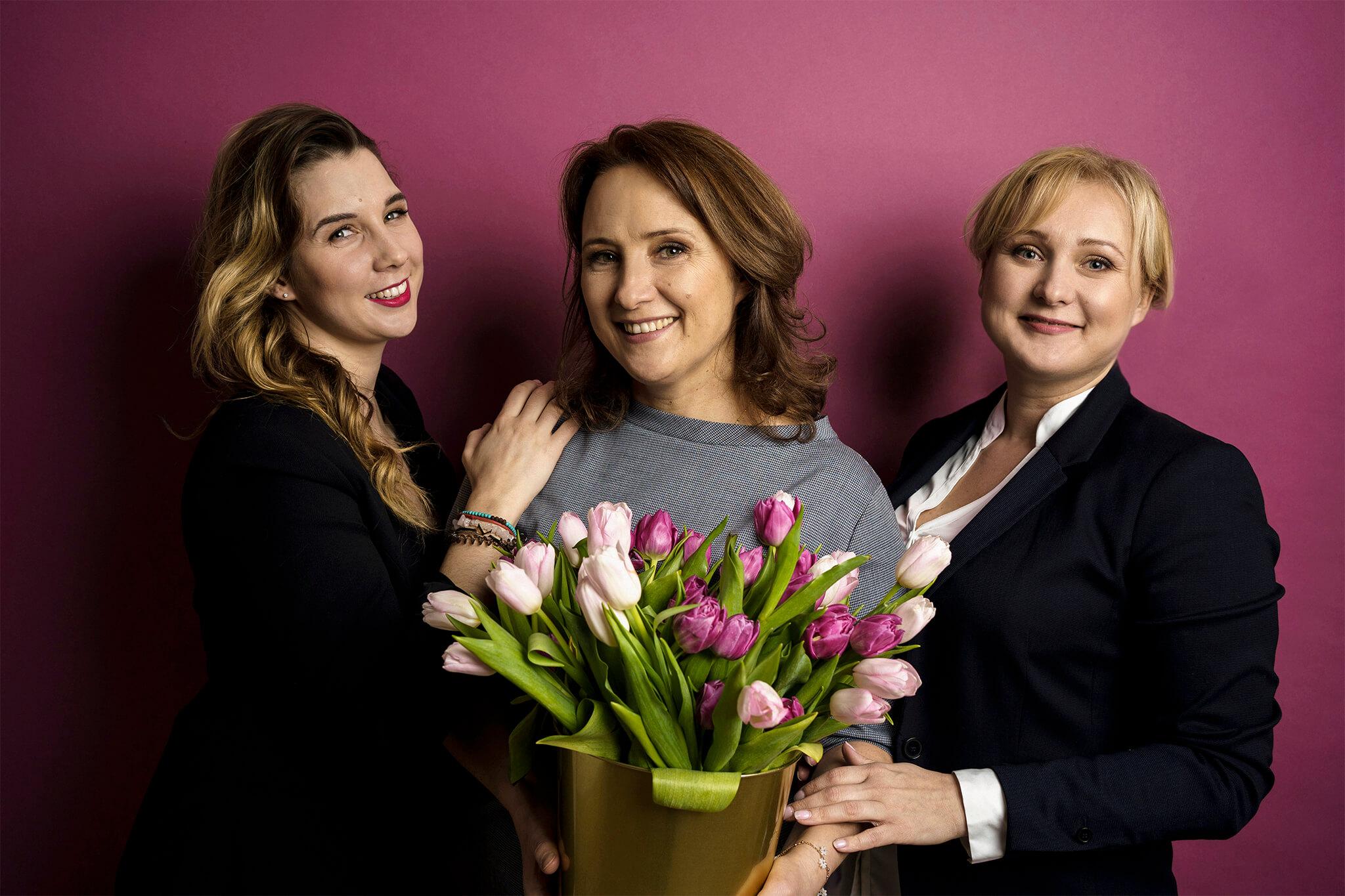 trzy kobiety na fioletowym tle z koszem tulipanów